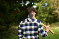 Rear view of man in forest carrying axe on shoulder Stock Photos
