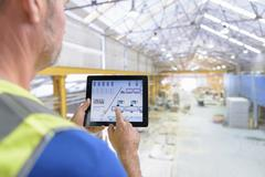 Worker using digital tablet to control robotic machinery in architectural stone Kuvituskuvat