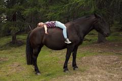 Girl lying bareback on horse in forest glade, Sattelbergalm, Tyrol, Austria Stock Photos
