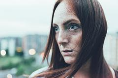Close up portrait of young freckled woman with long red hair and nose piercing Stock Photos