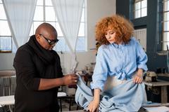 Male and female fashion designers examining material in design studio Stock Photos
