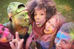 Portrait of group of friends at festival, covered in colourful powder paint Stock Photos