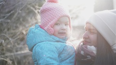 Calm Mother Holding Cute Little Daughter Enjoying Cold Sunny Weather in the Park Stock Footage