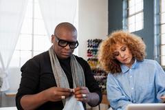 Male fashion designer examining material in design studio Stock Photos