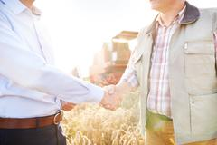Cropped view of farmer and businessman in wheat field shaking hands Kuvituskuvat