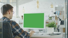 Close-up of a Man Sitting at His Desk with Green Screen PC on the Table.  Stock Footage