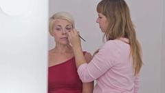Professional make-up artist applying eyeliner around the entire eye of model Stock Footage