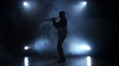 Trumpeter in a smoky studio playing a wind instrument Stock Footage