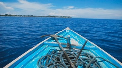 Blue boat with an anchor and a long rope on board, swaying from the wind Stock Footage