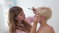 Professional make-up artist plucking eyebrows of client Stock Footage