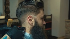 Unparalleled barber with a beard and a tattoo is cutting the hair of his client Stock Footage