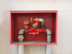 Building's fire hose connections with red handles in a red box Stock Photos