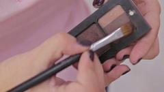 Close up shot. Make-up artist taking eye shadows from makeup eyeshadows palette Stock Footage