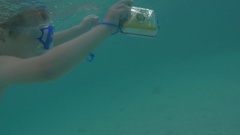 Child with camera in waterproof case bathing in the sea Stock Footage