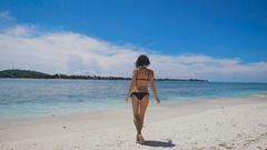Sexy brunnete in black bikini bathing in the sun on the beach of Bali island in Stock Footage