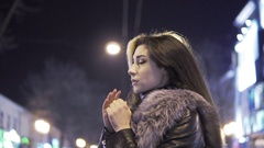 Young beautiful pretty woman heating her hands and waiting for someone at city Stock Footage