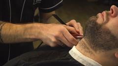 Shaving beard of man in barber shop Stock Footage