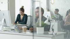 Weekday in a Busy Creative Bureau. Office People Working at Their Computers. Stock Footage