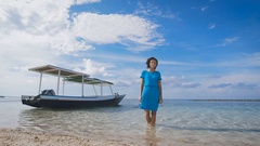 Attractive brunette in turquoise clothing is standing in the sea with Stock Footage