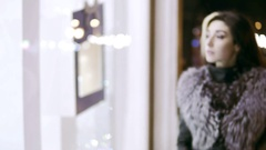 Winter dressed lady stands in front of the window display of expensive boutique Stock Footage