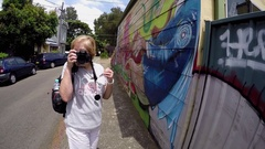 Tourist takes photo and walks past walls of graffiti Stock Footage