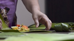 Woman wrapping tamales with banana leaves. Stock Footage
