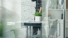 In a Creative Glassy Office Man Idly Walks and Talks On a Smartphone. Stock Footage