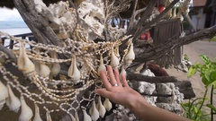 She travels to Bali. While walking she saw a tree on which hung the shells. She Stock Footage