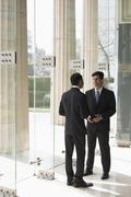 India, Two business men talking in building lobby Kuvituskuvat
