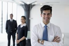 India, Smiling business man standing with arms crossed in front of colleagues Kuvituskuvat