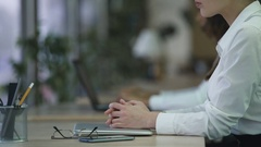 Woman sitting at office desk with hands folded on laptop, business day beginning Stock Footage