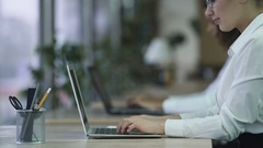 Successful female typing e-mail on laptop, smiling woman enjoying work at office Stock Footage