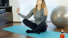 Girl doing yoga on the exercising mat in her joga, steadycam shot Stock Footage