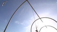 A woman in a white dress swings on traveling rings at Santa Monica beach , slow Stock Footage