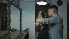 Unequaled barber with a beard and a tattoo is drying the hair of his client in a Stock Footage