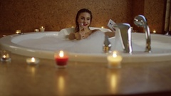 Woman with champagne in bath with foam taking selfie Stock Footage