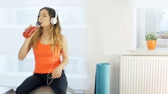Girl listening music and drinking energy drink while exercising on the ball Stock Footage