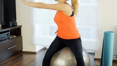 Girl sitting on the ball and exercise her arms, steadycam shot Stock Footage