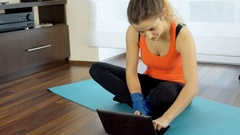 Girl using laptop during break in exercises, steadycam shot Stock Footage