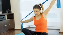 Girl exercising on the band and listening music, steadycam shot Stock Footage
