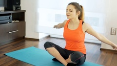 Girl exercising her arms while sitting on the mat and smiling to the camra, stea Stock Footage