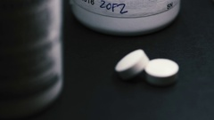 Pills spotlighted with pill bottles out of focus behind them Stock Footage