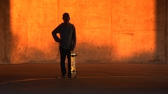 Silhouette of a young man skateboarding in a parking garage at sunset, super slo Stock Footage