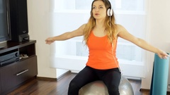 Girl listening music and exercising on the ball in her joga, steadycam shot Stock Footage