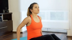 Girl sitting on the mat and doing exercises on band, steadycam shot Stock Footage