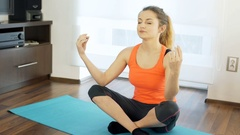 Girl doing yoga on exercising mat and looks calm, steadycam shot Stock Footage