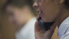 Pretty mixed race lady at hotel reception talking to guest on the phone, service Stock Footage