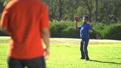 A father teaching his sons how to play American football , slow motion. Stock Footage
