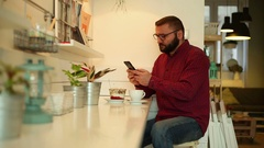 Man browsing internet on smartphone in the restaurant Stock Footage