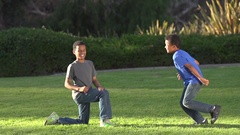 Two brothers giving each other a high five after kicking a football , super slow Stock Footage